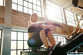 Young caucasian woman doing exercises on fitness machine in gym. Female using rowing machine at  fitness club.