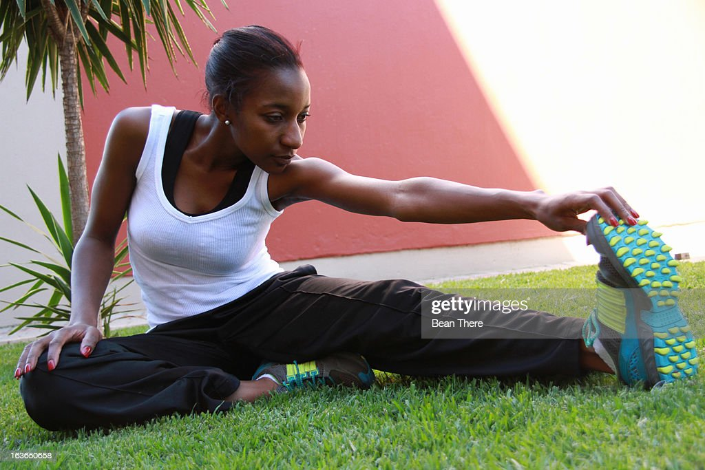 Young woman doing hamstring stretch, Johannesburg, South Africa : Stock Photo