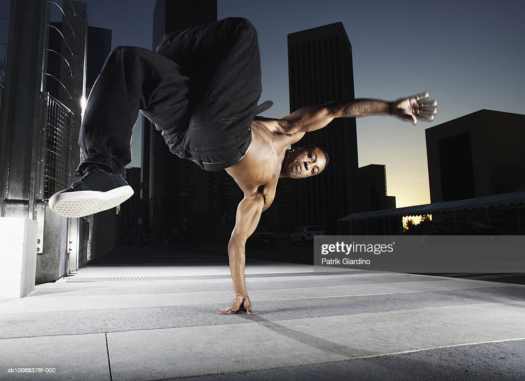 Young woman doing handstand on street at dusk, portrait : Stock Photo