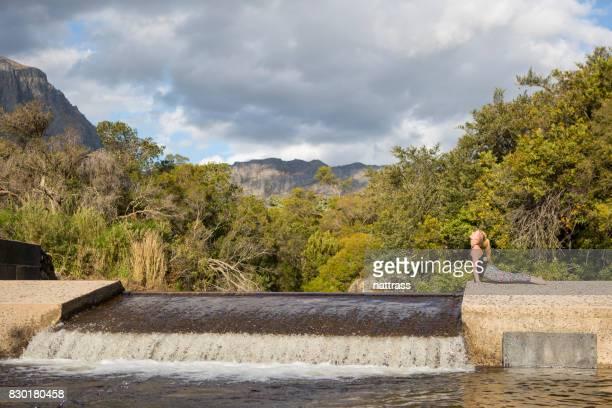 Jeune femme faisant son yoga à l'extérieur de la rivière