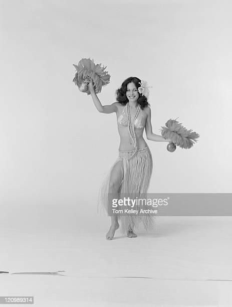 Jeune femme en train de danse hula, souriant, portrait