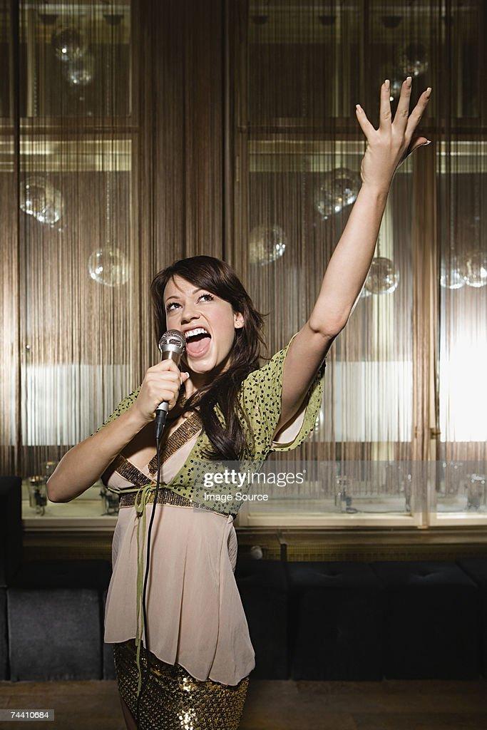Young woman doing karaoke : Stock Photo