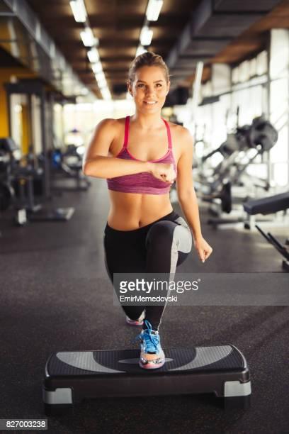 Jeune femme faisant des mouvements brusques sur matériel d'aérobic step au gymnase