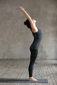 Young woman practicing yoga, doing mountain exercise, Tadasana pose, working out, wearing sportswear, black pants and top, indoor full length, gray wall in yoga studio. Side view photo