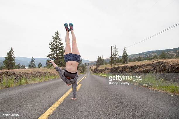 Young woman doing one handed handstand in road