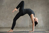 Young woman practicing yoga, doing Bridge exercise, One legged Wheel pose, working out, wearing sportswear, black pants and top, indoor full length, gray wall in yoga studio