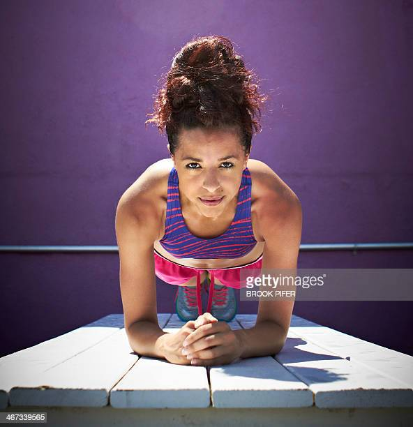Young woman doing plank core pose