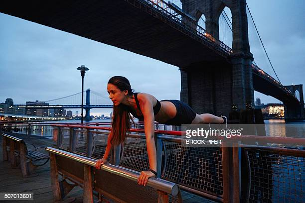Young woman doing plank pose in urban setting