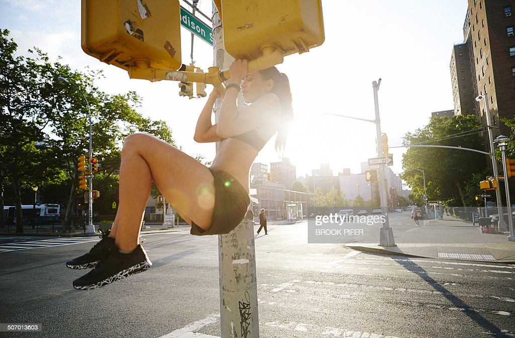 Young woman doing pull up in urban setting : Stock Photo