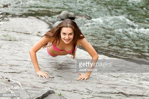 Young woman doing push ups : Stock Photo