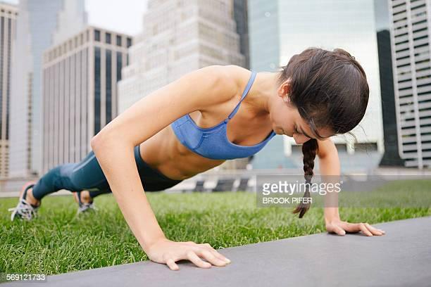 Young woman doing push-ups in urban setting
