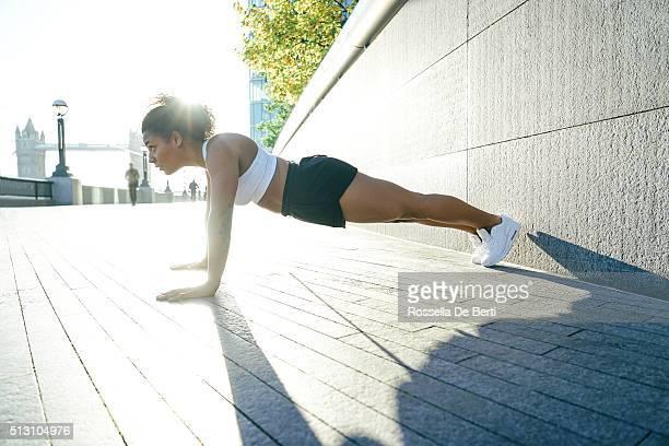 Mujer joven haciendo Pushups al aire libre en el temprano en la mañana