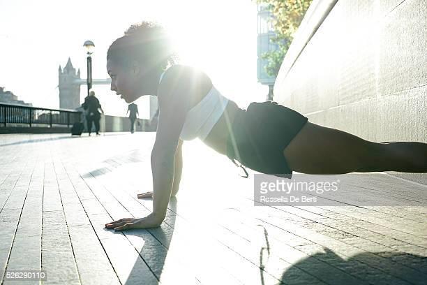 Giovane donna fare push-up all'aperto al mattino presto