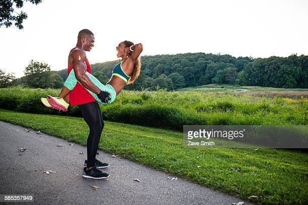 Young woman doing sit up training whilst straddling boyfriend