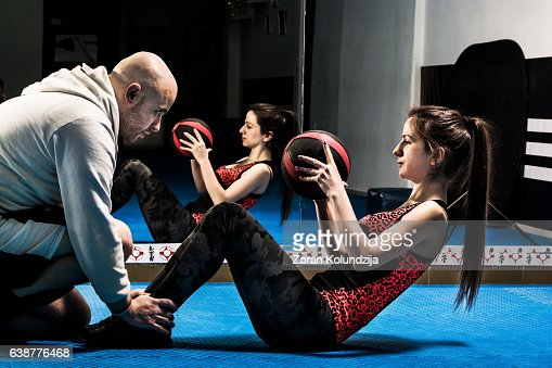Young woman doing sit-ups holding medicine ball in gym