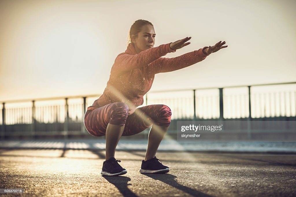 Young woman doing squats on a road at sunset. : Stock Photo