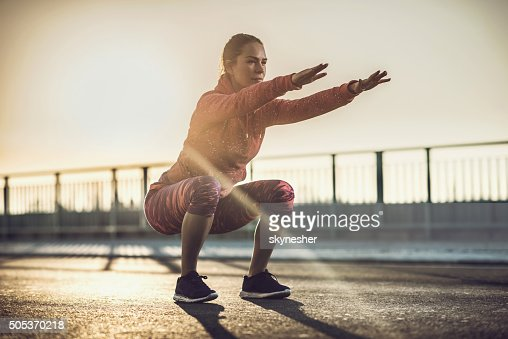 Young woman doing squats on a road at sunset.