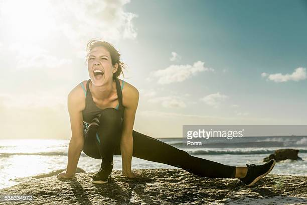 Young woman doing stretching exercise on rock