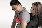 Young woman doing the first aid to a man over a white background