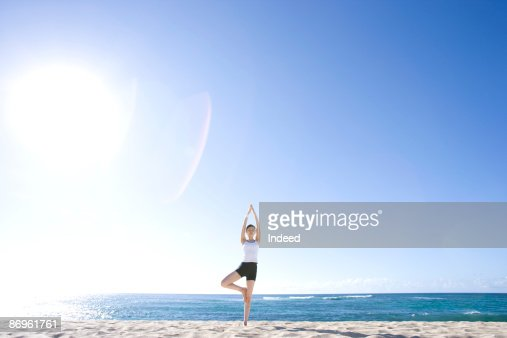 Young woman doing tree pose of yoga asana on beach : Stock Photo