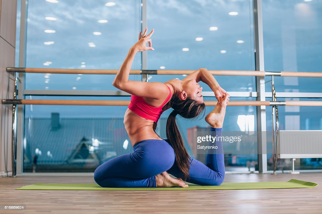 Young woman doing yoga exercises on mat at gym : Stock Photo