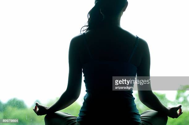 Young woman doing yoga in front of window