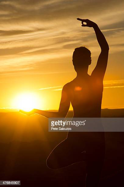 Young woman doing yoga in sunlight, Moab, Utah, USA