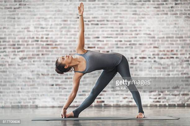 Mujer joven haciendo ejercicios de Yoga meditación y de estiramiento