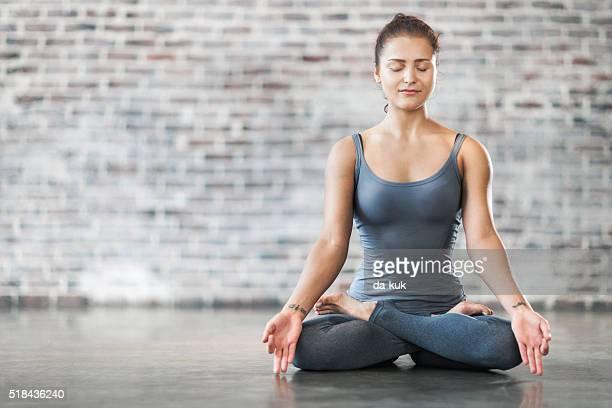 Mujer joven haciendo ejercicio de meditación de Yoga. Posición del loto