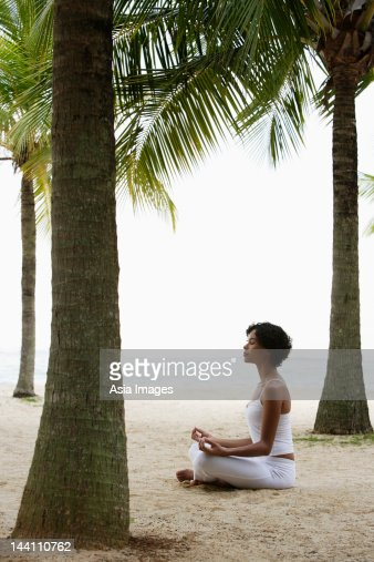 Young woman doing yoga on beach, under coconut trees, meditating. : Stock Photo