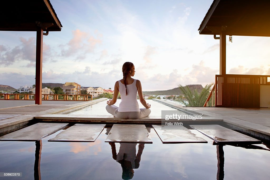 Young woman doing yoga on patio : Stock Photo