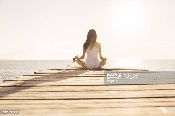 Mujer joven haciendo yoga en el muelle