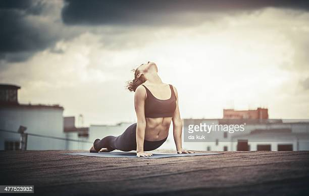 Young woman doing Yoga outdoors on a rooftop at sunset