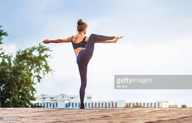 Giovane donna facendo yoga all'aperto su un tetto