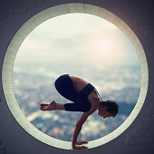 young woman doing bakasana in the round window