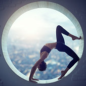 Young woman doing yoga in the round window