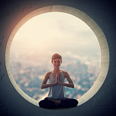 Young woman sitting at lotus posture in the round window