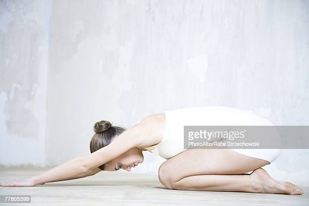 Young woman doing yoga pose, side view, full length