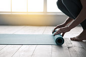 Young woman doing yoga twisting mat indoors near window
