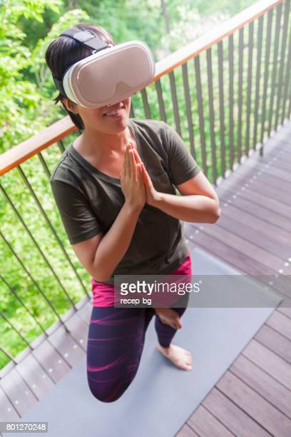 Young Woman Doing Yoga With Virtual Reality Device