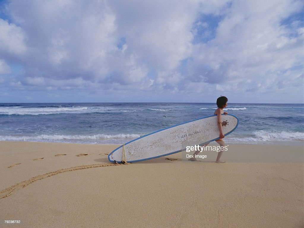 Young woman dragging surfboard on beach : Stock Photo