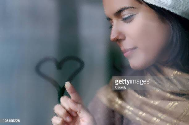 Junge Frau zeichnen Herz auf einem nebeligen Fenster