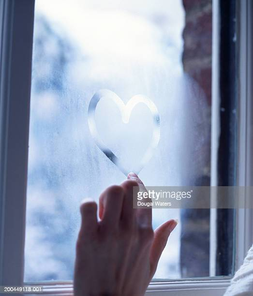 Young woman drawing heart on steamed window, close-up