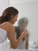Young woman drawing heart shape in foggy bathroom mirror