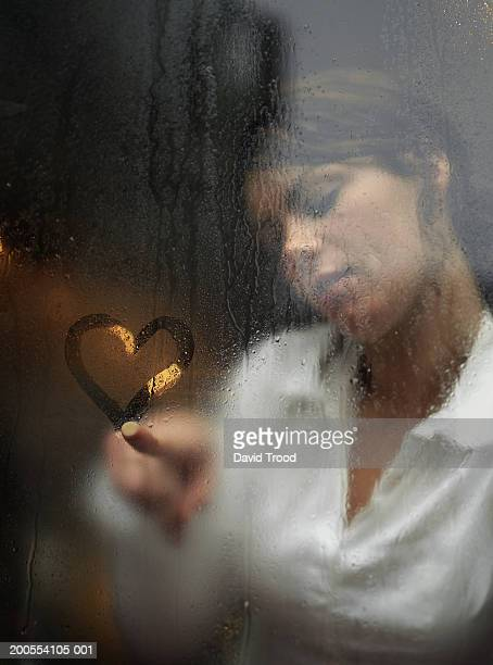 Young woman drawing heart shape with finger on fogged glass