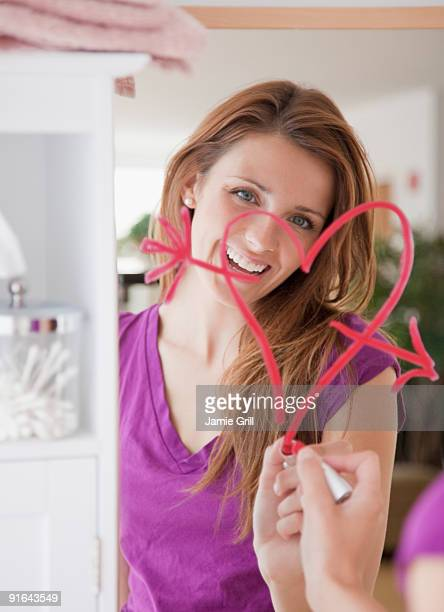 Young woman drawing heart with lipstick on mirror
