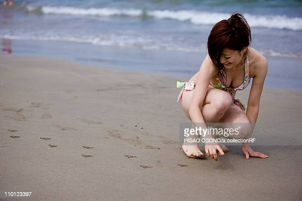 Young Woman Drawing on Sand