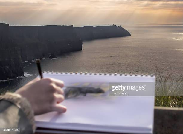 Young woman drawing scenic View Of Cliffs Of Moher, Ireland