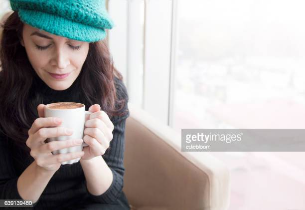 Young woman dreaming with cup of coffee