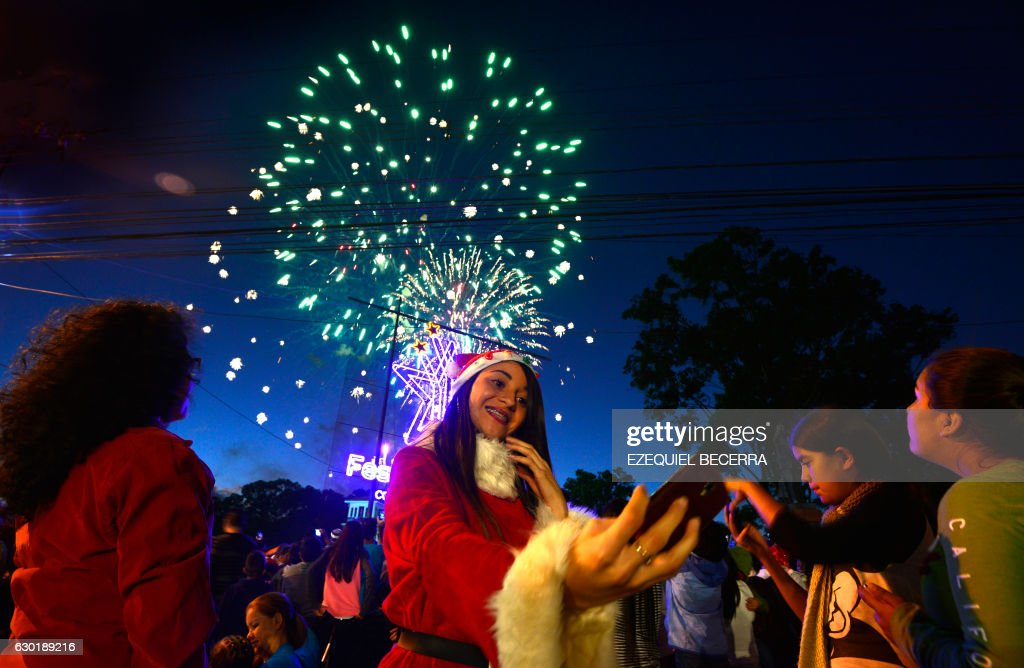 A young woman dressed as Santa Claus takes selfies with fireworks background during the Festival of Light in the main streets of San Jose, late at night on December 17, 2016. /